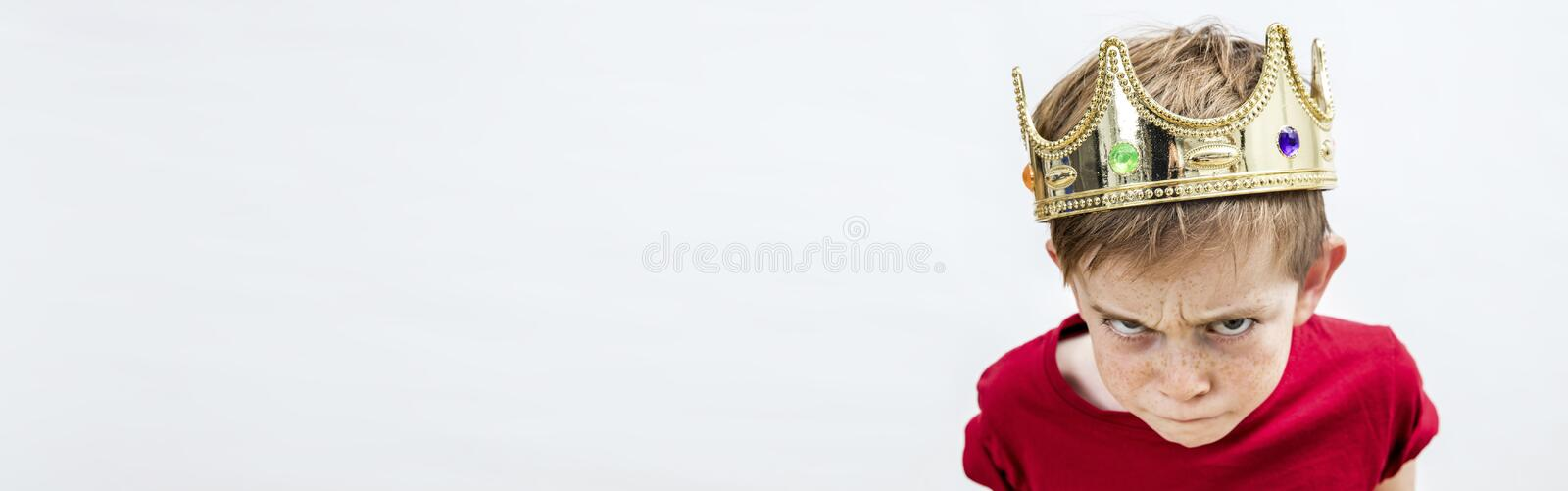 Banner of rebellious spoiled kid for mad attitude, white background. Long banner of rebellious beautiful spoiled kid with frowning freckles wearing a king crown stock image
