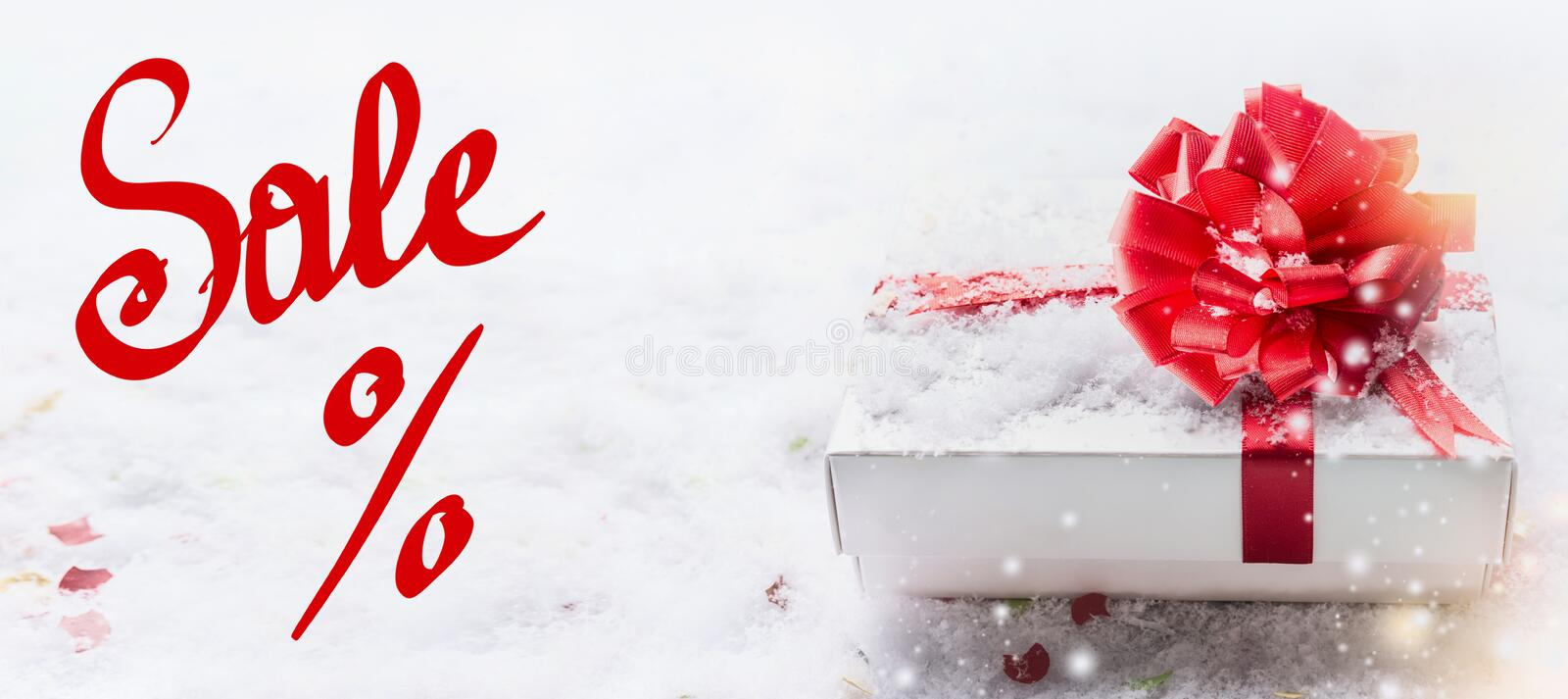 Banner with red Sale % text lettering, white gift box, red bow on snow with bokeh and snowfall. Valentines day coupon, sale and royalty free stock images