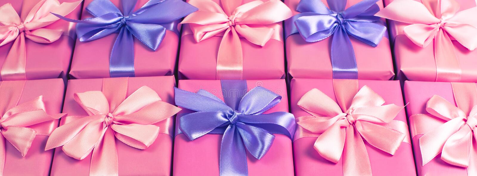 Banner Rows of boxes with gifts decoration ribbon satin bow pink A top view of Flat lay toning stock image