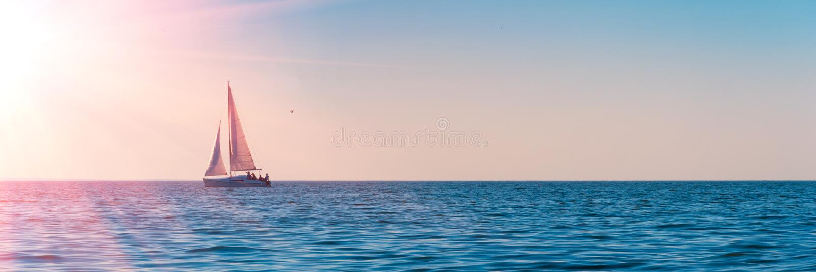 Banner 3:1. Sailboat in the sea in the evening sunlight over sky background. Luxury summer adventure or active vacation concept. stock image