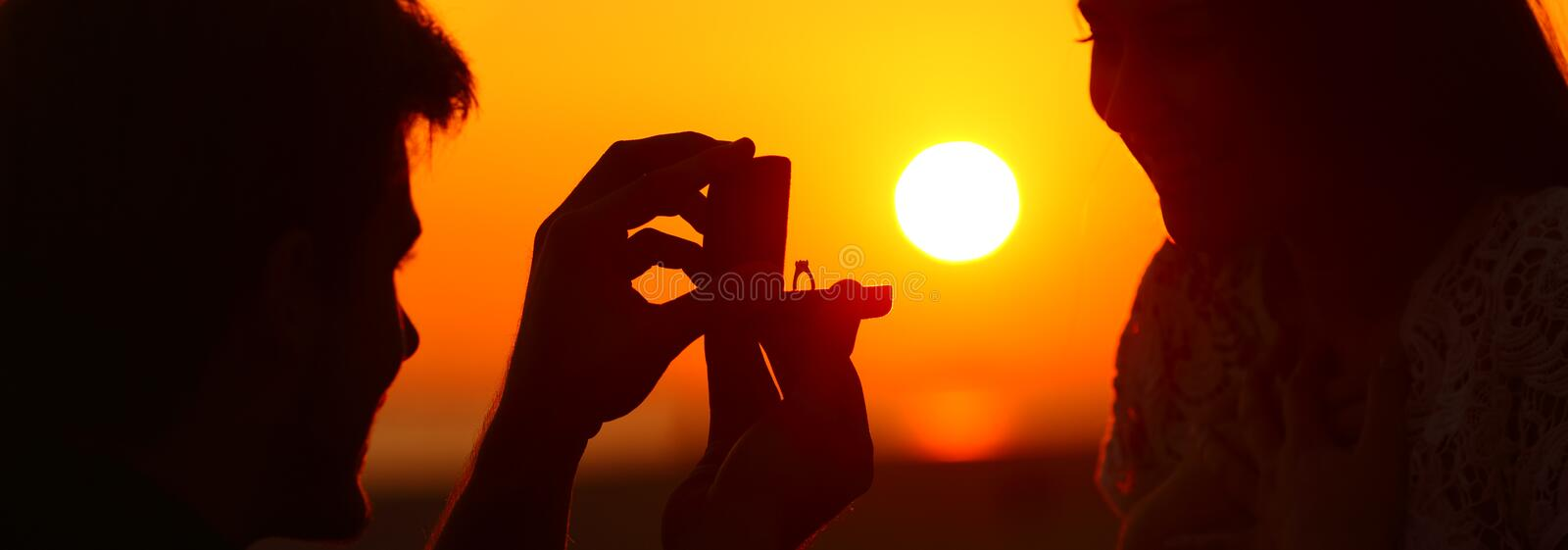 Banner of silhouette of marriage proposal at sunset. Back light banner of silhouette of marriage proposal offering engagement ring at sunset stock photography