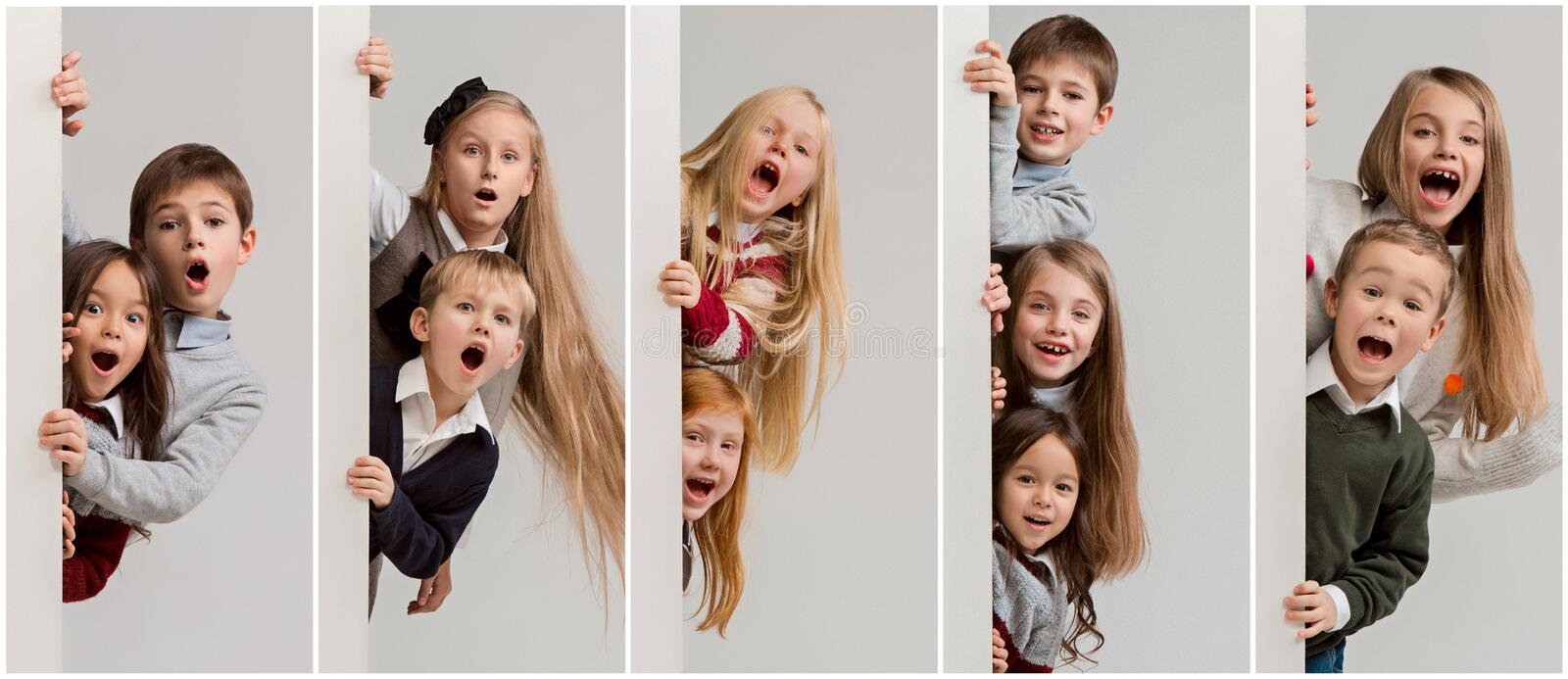 Banner with a surprised children peeking at the edge. With copyspace. The portrait of cute little kids boy and girls looking at camera against white studio wall royalty free stock photo