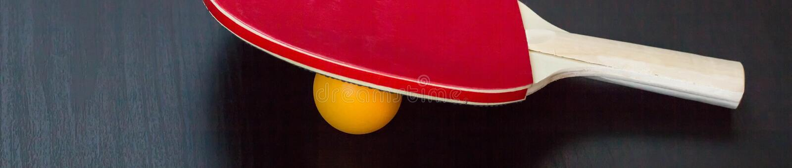 banner of table tennis or ping pong racket and ball on a black background stock photos