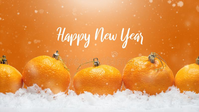 Banner with tangerines in the form of Christmas decorations on the snow, with falling snow. Happy Christmas or Happy New Year, royalty free stock photography
