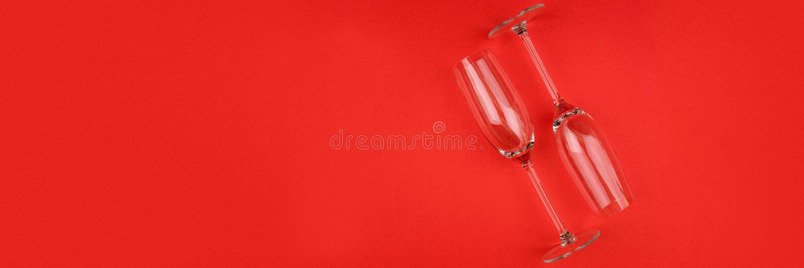 Banner 3:1 for Web. Wineglasses for champagne lying on red paper background. New Year celebration concept. stock images