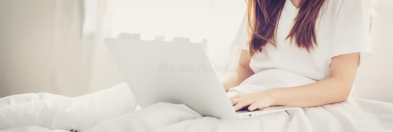 Banner website beautiful asian young woman setting on bed using. Laptop computer at bedroom for leisure and relax, freelance with girl working notebook royalty free stock photos