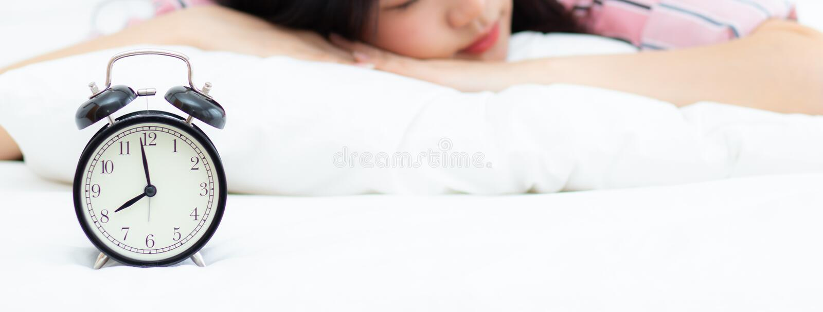 Banner website closeup alarm clock and beautiful asian young woman in morning, wake up for sleep with alarm clock, relax and stock photo