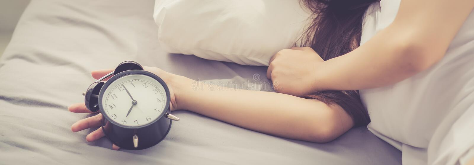 Banner website closeup asian young woman turn off alarm clock in royalty free stock photography