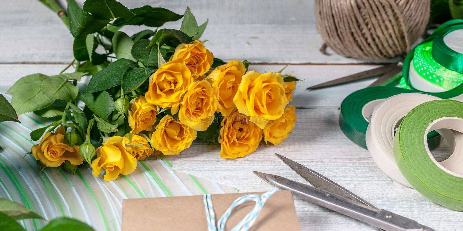 Banner. Workplace florist. Elegant yellow rose, scissors, gift wrap and other accessories on the horizontal wooden background stock photography