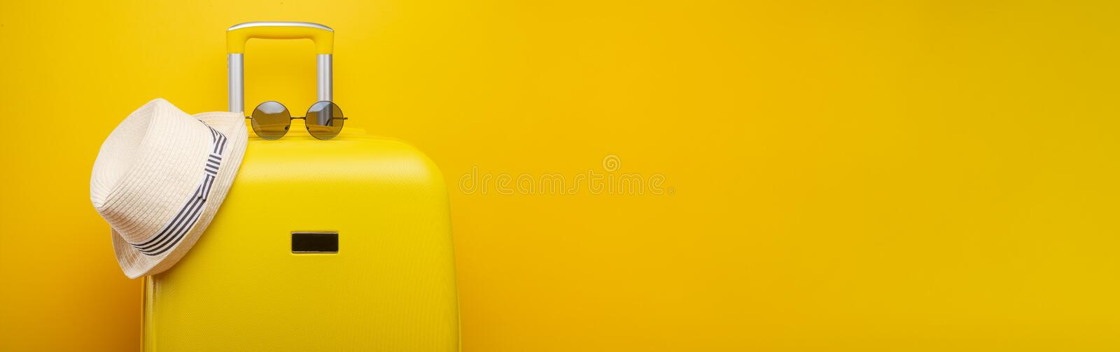 Banner yellow suitcase, with a hat for recreation, the beach and sunglasses. Travel Things Concept Festive Adventure Travel, on. Yellow background stock image