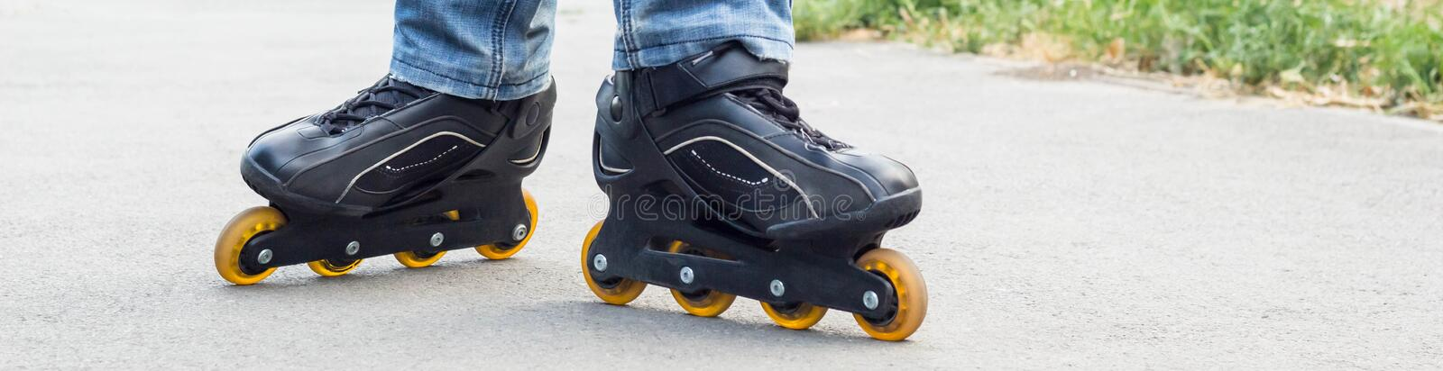 banner of Young man in blue jeans riding roller skates in the city. Close up legs royalty free stock image