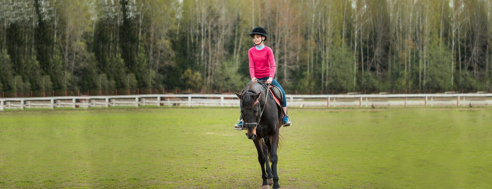 Young sportswoman riding horse in equestrian show jumps competition. Teenage girl ride a horse royalty free stock images