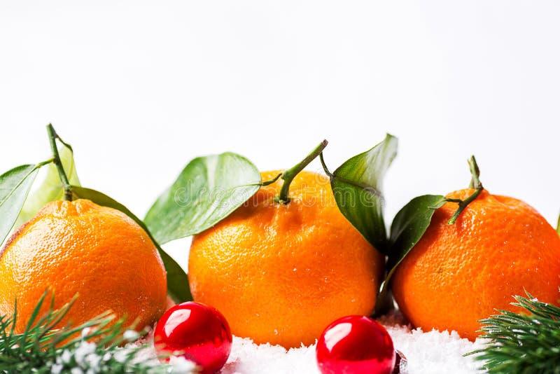 Bannière d'affiche de carte de voeux de nouvelles années de Noël avec les mandarines fraîches sur la tige avec les boules vertes  photographie stock