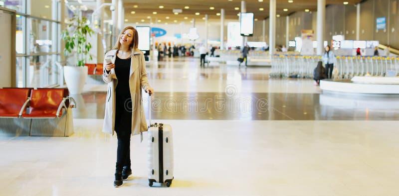 Bannière de la jeune femme avec la mallette marchant dans le hall de attente à l'aéroport image stock