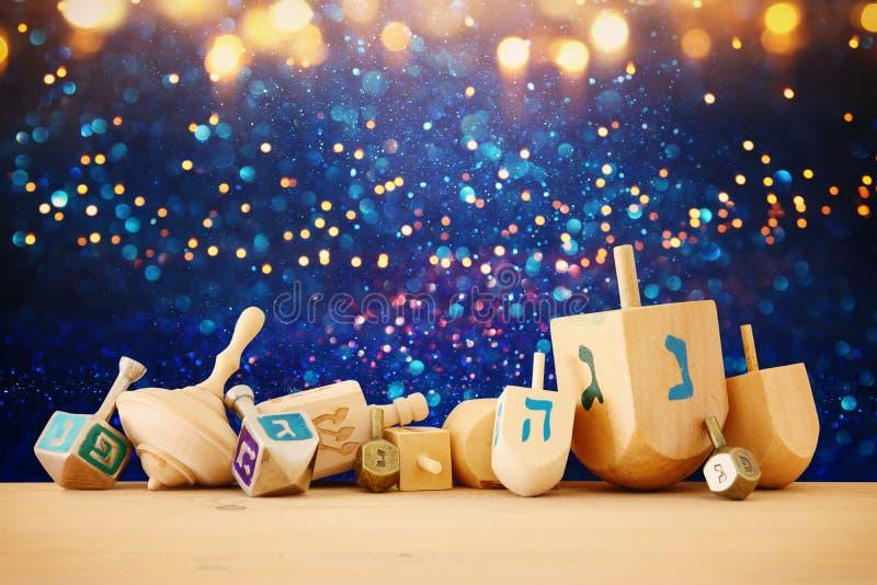 Bannière des vacances juives Hanoucca avec les dreidels en bois et le x28 ; top& de rotation x29 ; au-dessus du fond brillant de