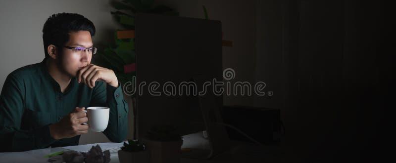 Bannière du café potable de jeune homme asiatique attirant se reposant sur la table de bureau regardant l'ordinateur portable dan images libres de droits