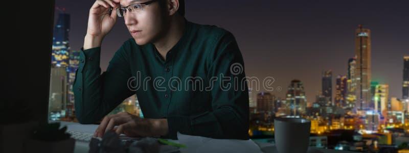 Bannière du jeune homme asiatique s'asseyant sur le travail de table de bureau en retard et dur avec l'ordinateur portable d'ordi images stock
