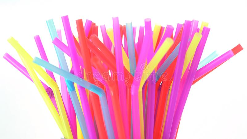 Banning plastic straws enviromental concerns concept. Banning plastic straws enviromental concerns concept, many straws against white background stock images