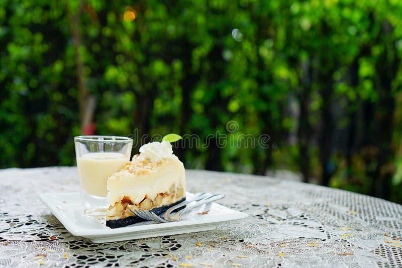 Banoffee饼用焦糖调味汁,绿色庭院背景 免版税库存图片