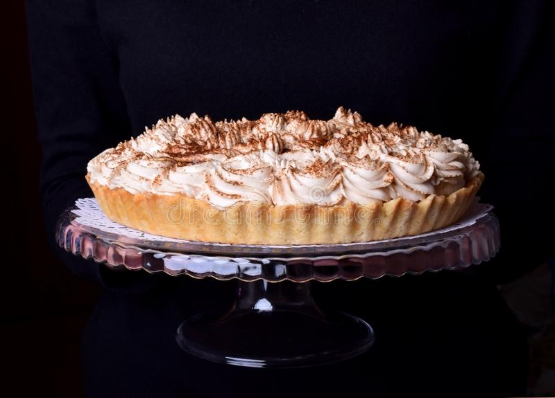 Banoffee pie topped with whipped cream and sprinkled with grounded coffee royalty free stock images