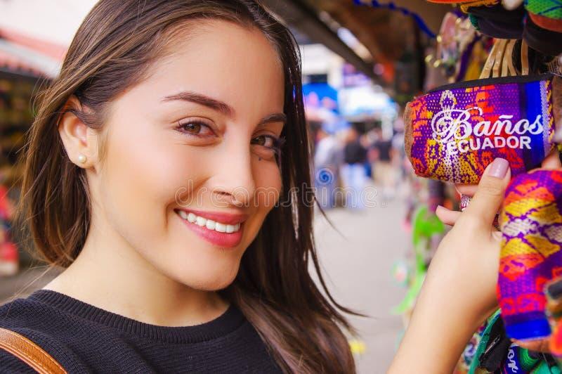 BANOS,厄瓜多尔, 2018年8月, 17日:关闭拿着在她的手上印地安手工制造钱包的微笑的妇女在工艺 免版税库存图片