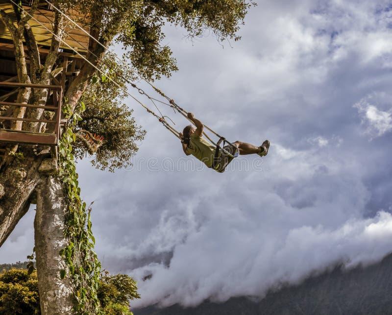 Banos, Equateur - 24 septembre 2018 - personne monte l'oscillation au-dessus d'un abîme, avec un sentiment du vol photographie stock libre de droits