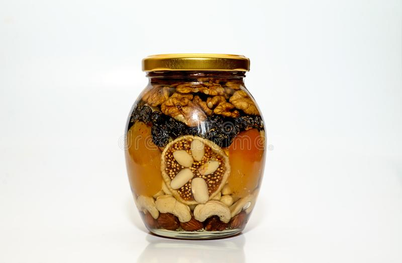 Banque avec du miel et des écrous image stock