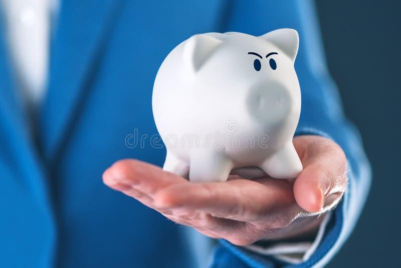 Banque de pièce de monnaie porcine fâchée dans la main du ` s de femme d'affaires image stock