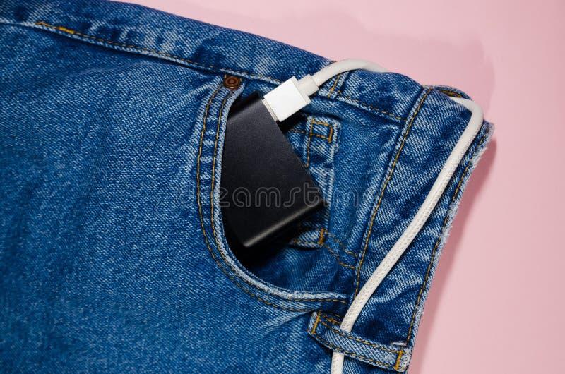 Banque de puissance dans des jeans photo stock