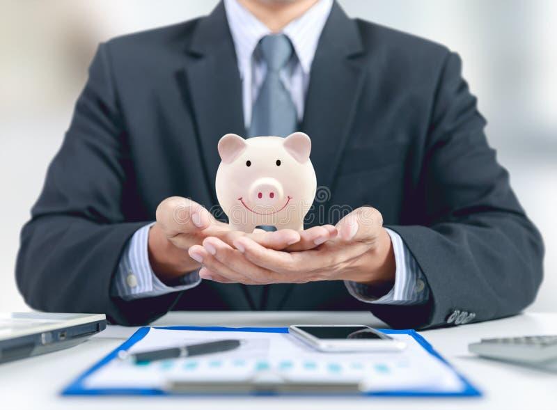 Banque en céramique porcine de rose actuel d'homme d'affaires en main photographie stock