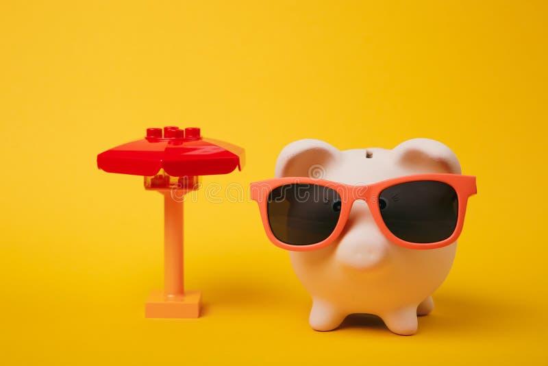 Banque porcine rose d'argent avec des lunettes de soleil, parapluie de jouet sur le fond jaune de mur Investissement d'accumulati photos libres de droits