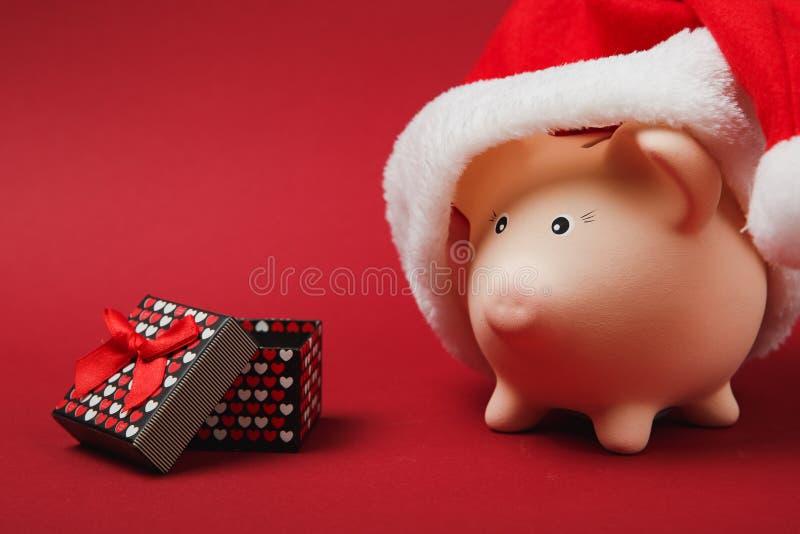 Banque porcine rose d'argent avec le chapeau de Noël, boîte actuelle avec le ruban de cadeau sur le fond rouge Accumulation d'arg image libre de droits