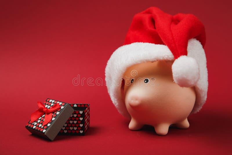 Banque porcine rose d'argent avec le chapeau de Noël, boîte actuelle avec le ruban de cadeau sur le fond rouge Accumulation d'arg photographie stock libre de droits