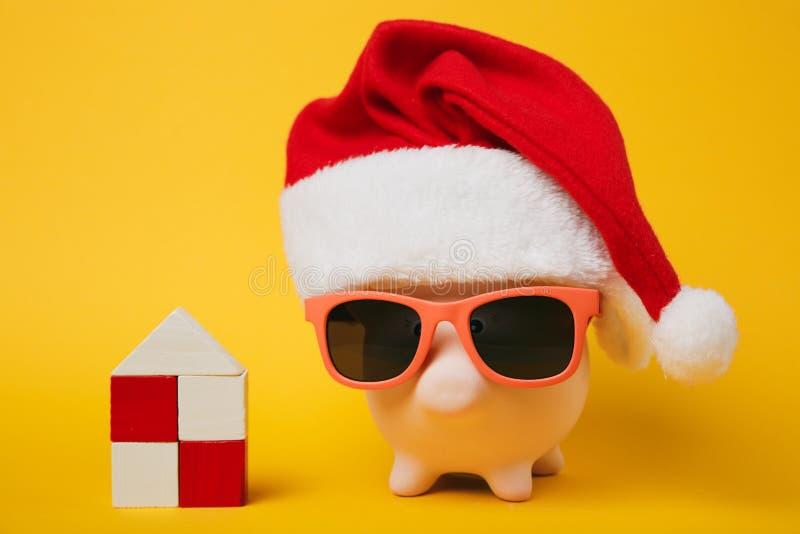Banque porcine rose d'argent avec le chapeau de Noël de lunettes de soleil, maison en bois de jouet sur le fond jaune de mur Arge image libre de droits