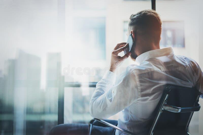 Banqueiro à moda que faz a chamada móvel no sótão moderno após o dia do trabalho Equipe o assento na cadeira e a vista para fora  fotografia de stock