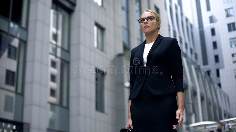 Banqueiro de mulher irritado com o smartphone, obtendo más notícias, motivação ao trabalho duro fotografia de stock