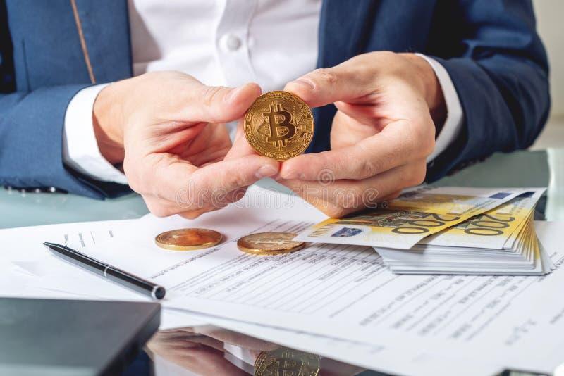 Banqueiro do homem de negócios que senta na tabela com terra arrendada de papéis um bitcoin da moeda Troca e venda do cryptocurre imagem de stock royalty free