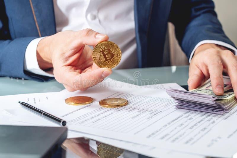 Banqueiro do homem de negócios que senta na tabela com terra arrendada de papéis um bitcoin da moeda Troca e venda do cryptocurre fotos de stock royalty free