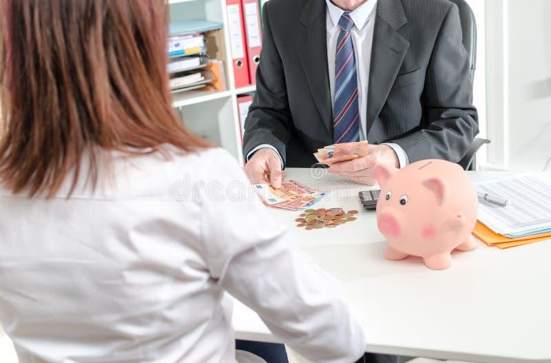 Banqueiro que conta economias de seu cliente fotografia de stock