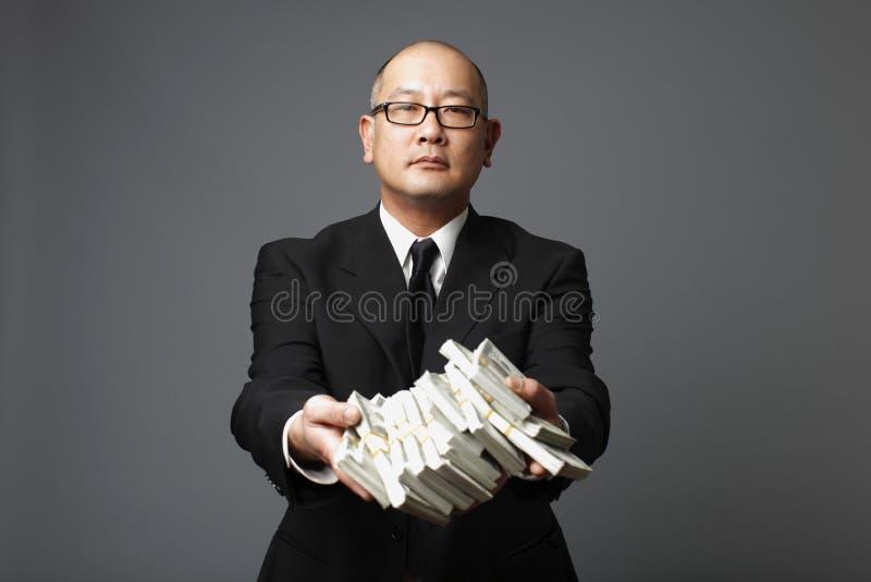 Banqueiro que distribui o dinheiro imagens de stock