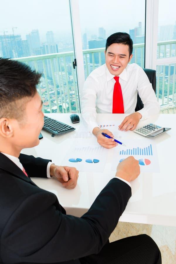 Banquero asiático que aconseja la inversión financiera foto de archivo libre de regalías