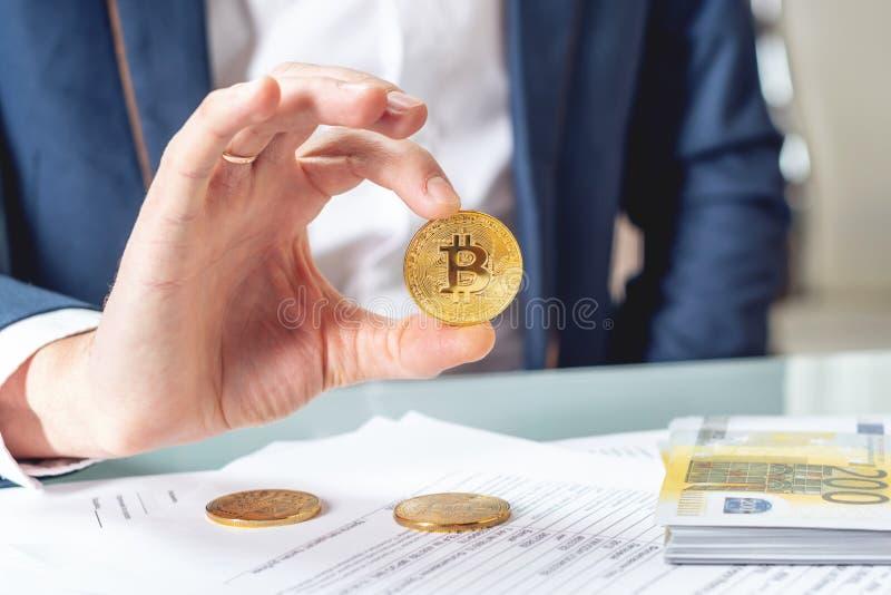 Banquero del hombre de negocios que sienta en la tabla con la tenencia de papeles un bitcoin de la moneda Intercambio y venta del fotos de archivo