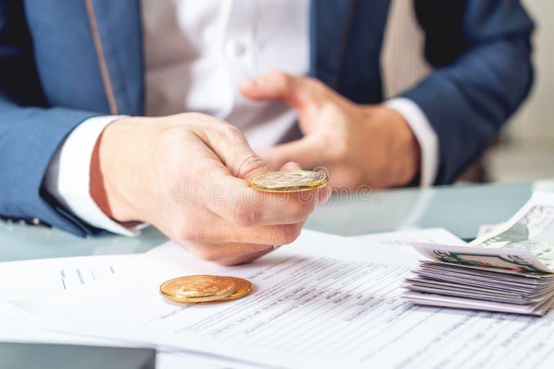 Banquero del hombre de negocios que sienta en la tabla con la tenencia de papeles un bitcoin de la moneda Intercambio y venta del imagen de archivo