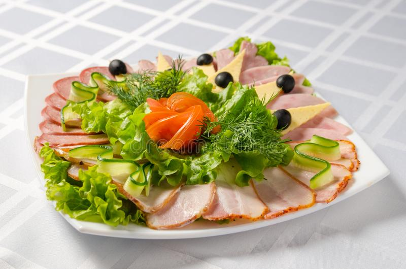 Banquet cutting with ham, meat delicacies, cheese, sausage smoked, olive, lettuce and tomato on white dish stock photography