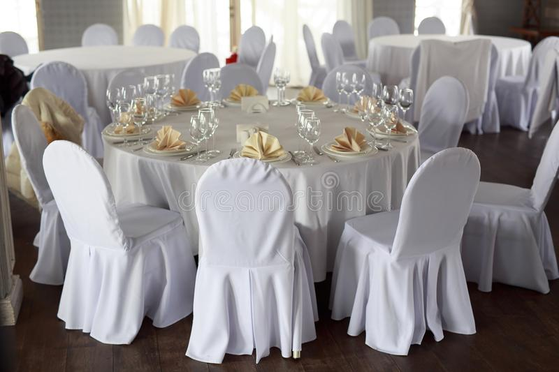 Banquet hall chairs, white tablecloth, food table, table setting, empty wine glasses, Banquet hall without people. Wooden floor royalty free stock images