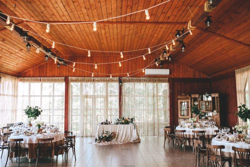 Banquet il corridoio di legno per le nozze rustiche con le tavole decorate rotonde, sedie viennesi con le foglie fiorite e fotografie stock