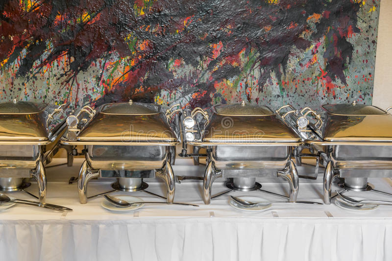 Banquet table with chafing dish heaters. White Plates stock photos
