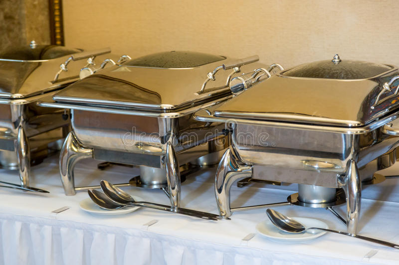 Banquet table with chafing dish heaters. White Plates stock images