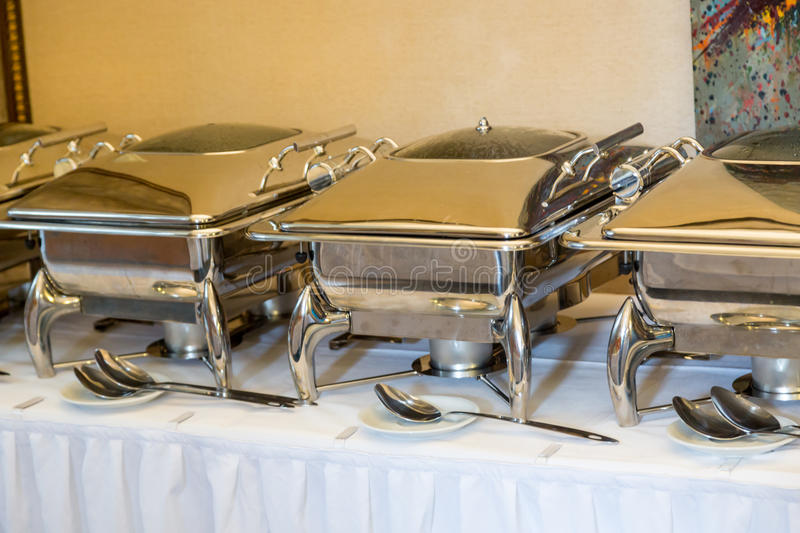 Banquet table with chafing dish heaters. White Plates stock image