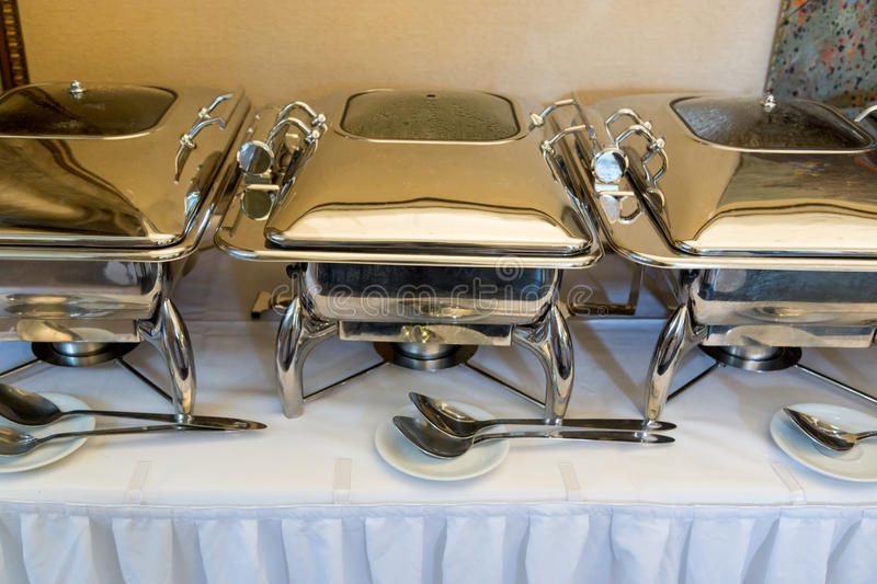 Banquet table with chafing dish heaters. White Plates stock photo